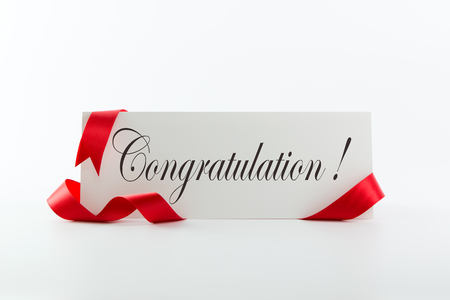 Congratulations note or greeting card with red ribbon over white background