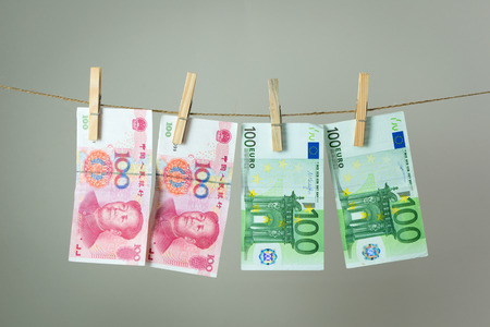 Euro and China Yuan banknotes hanging on rope for money laundering concept