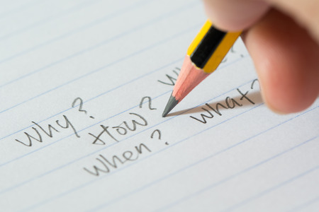 unanswered: Hand writing questions on paper for brainstorming, uncertainty or decision making concept Stock Photo