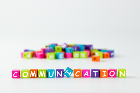 communicating: Communication word spelled with colourful wooden block over white background Stock Photo