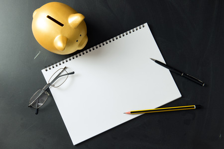 blank note: Blank note book with golden piggy bank, glasses, pen and pencil over black background Stock Photo
