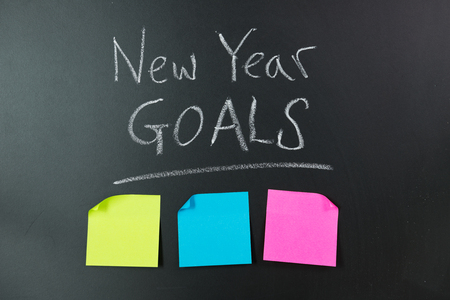 note pad: New year goals lists with blank sticky pad note on chalkboard
