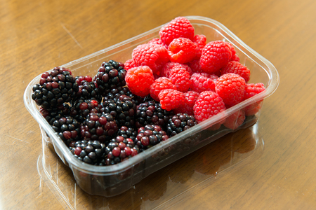 Close up of fresh raspberries and blackberries in plastic container