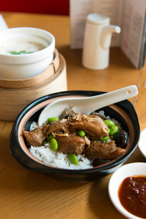 Set of claypot chicken rice served with creamy soup and chili sauce Stock Photo