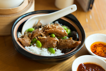 Close up of claypot chicken rice served with mushroom and green peas