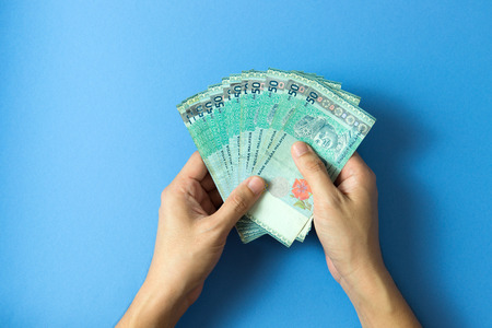 Hand with fifty Ringgit Malaysia currency notes over blue background