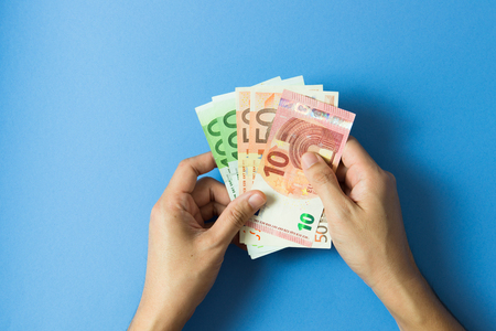 Hand with Euro currency notes over blue background
