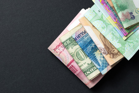 global rates: Foreign currency banknotes over black background