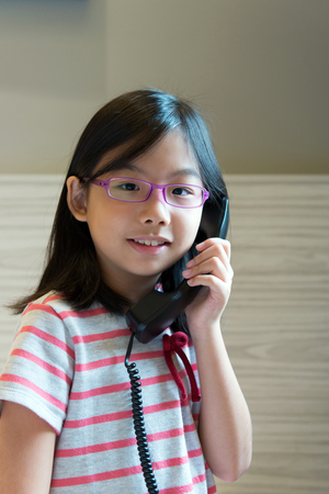 Portrait of Asian little girl speaking on the phone Stock Photo