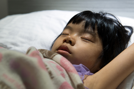 Close up of Asian child sleeping soundly on bed photo