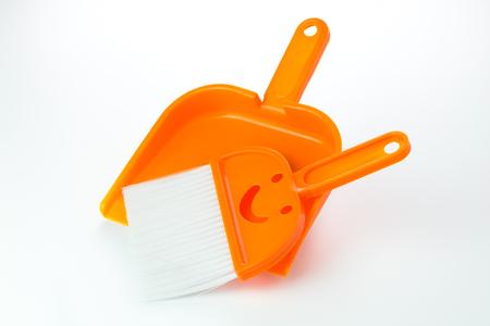 Kleine oranje bezem en blik via witte achtergrond Stockfoto
