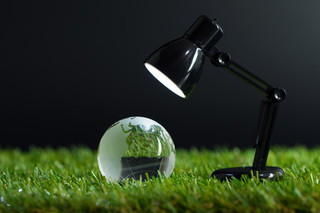 environmental conversation: Table lamp lights up crystal globe on the grass Stock Photo