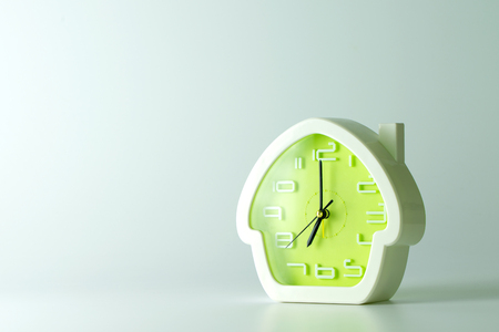 grey house: House shaped alarm clock isolated in grey background