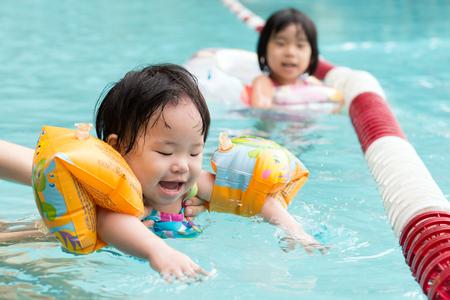 プールで泳いで腕章児の小さなアジア 写真素材