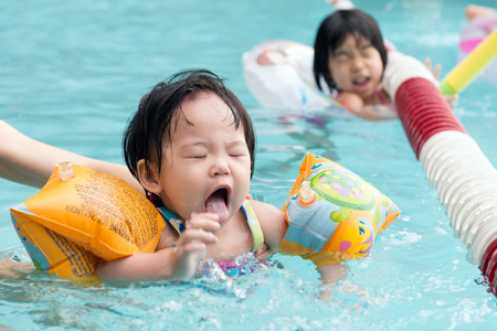 Little Asian child with armbands swimming in the pool photo