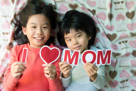 Two Asian kids holding I Love Mom wording for happy mother's day theme photo