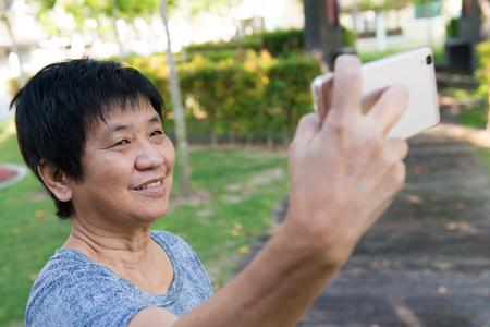 Happy senior woman taking selfie with smart phone at the park