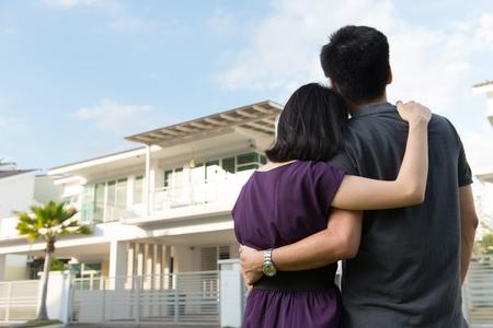 Paar dat zich in de voorkant van droomhuis in de moderne woonhuizen Stockfoto