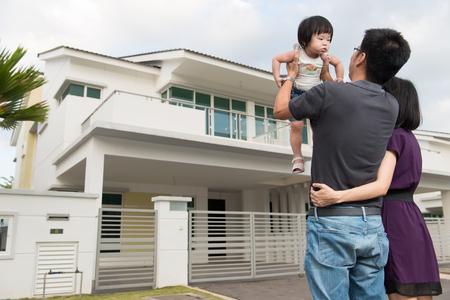 Jonge ouders met een peuter die zich voor moderne woonwijk Stockfoto