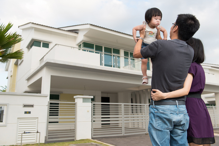 Young parents with toddler standing in front of modern residential area photo