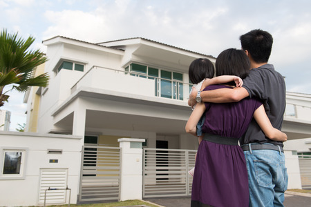 Junge Eltern mit Kleinkind vor dem modernen Wohngebiet stehen Standard-Bild