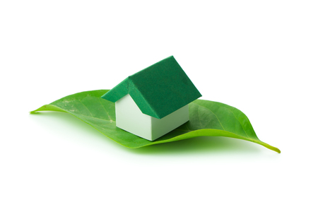 environmental conversation: Miniature green house on leaf over white background Stock Photo