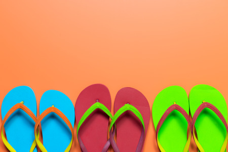 Multicolor flip flops on orange background, with copy space
