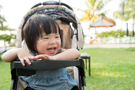 Little Asian toddler in sitting stroller at the park