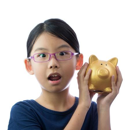 coinbank: Little Asian girl holding golden piggy bank with surprise face Stock Photo