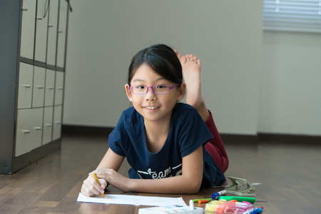 Little Asian girl is drawing with crayon on the floor