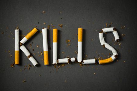 Das Wort tötet mit Zigaretten auf schwarzem Hintergrund