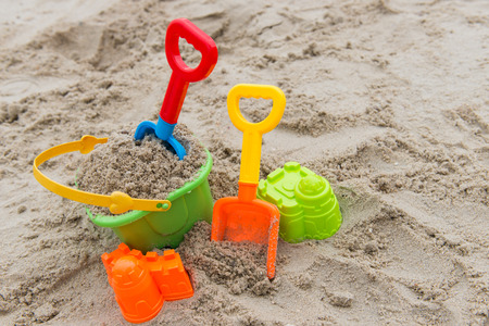Colourful summer beach toys on sandy beach