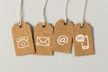 Strona internetowa kontaktuje się z nami ikony na brązowych tagach na szarym tle Zdjęcie Seryjne