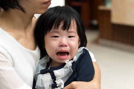 그녀의 작은 우는 아이를 껴안는 아시아 어머니 스톡 콘텐츠