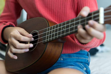 Close up of view of little girl's hand playing ukulele 스톡 콘텐츠