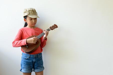 Portrait of little Asian girl playing ukulele over grey background Stock Photo