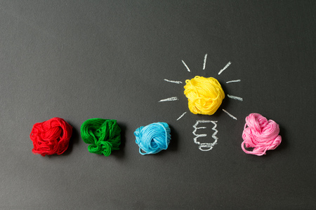 Light bulb in a row of multicolor yarn balls over black background 写真素材