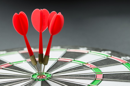 Three red darts pinned right on the center of target Stock Photo - 82147572