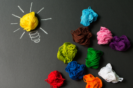 Great idea concept with light bulb among multicolor yarn balls over black background