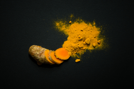 Turmeric roots and turmeric powder isolated on black background Stock Photo