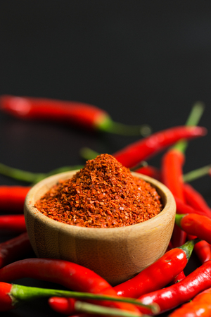 Red chili peppers and chili flakes on black background Фото со стока