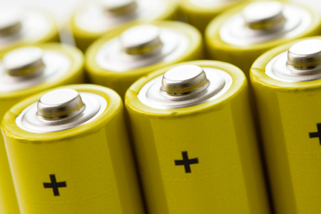 Group of yellow alkaline batteries forming background 스톡 콘텐츠