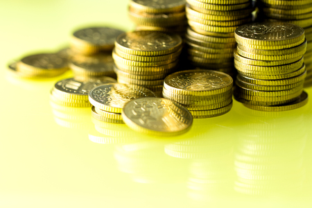 Pile of gold coins over gold tone background