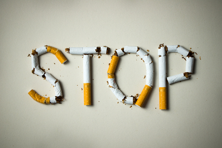 The word stop spelled using cigarettes on grey background