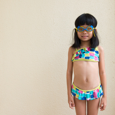 Little girl wearing swimming suit and goggles ready to swim Standard-Bild