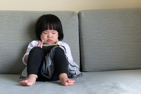 Little girl sitting on the sofa playing smart phone