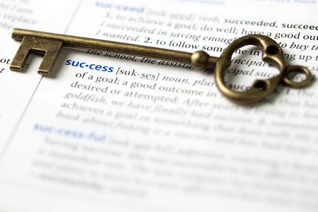 Close up of antique key placed on the definition of success