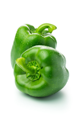 Two green bell peppers with water droplets isolated on white background Imagens