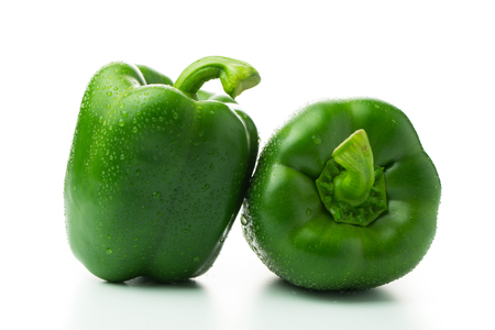 Two green bell peppers with water droplets isolated on white background Stock Photo