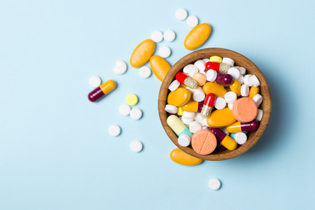 Assorted pharmaceutical medicine pills, tablets and capsules on wooden bowl Stock Photo